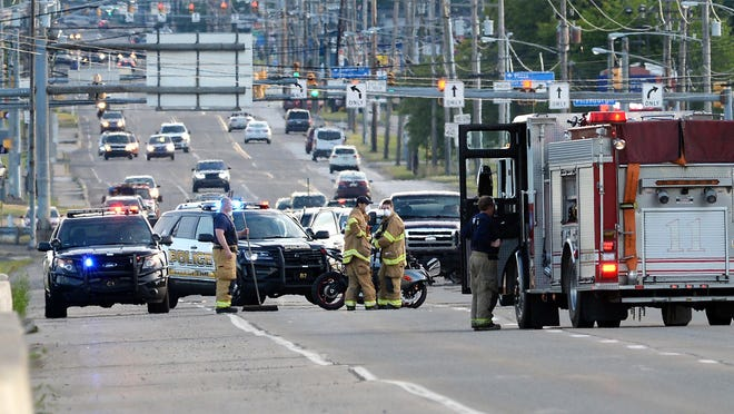 Erie firefighters, center, Erie police and EmergyCare personnel assist a motorcyclist injured in a crash on West 12th Street, eastbound, between the Interstate 79 on-ramp and exit. The crash closed West 12th Street between the on-ramp and exit.