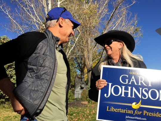 Libertarian presidential candidate Gary Johnson talks with retired lab worker Marquita Sena of Pojoaque, right, in Santa Fe, on Tuesday.