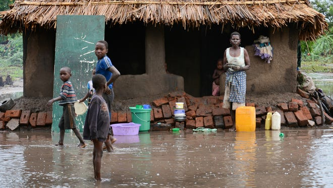 On Jan, 15, 2015, a family that survived flood waters wait outside they home for relief teams in the southern district of Chikwawa, near Blantyre, Malawi.
