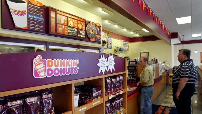 Customers line up to order doughnuts from at a Dunkin' Donuts store.