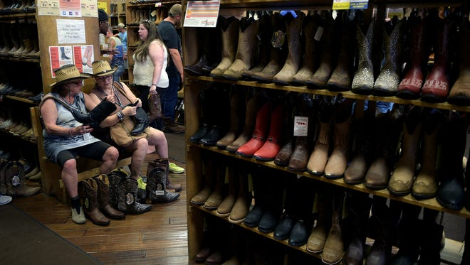 Marlieeas Papes, left, and Rita Gsilla, both from Switzerland, try on boots at Boot Country during CMA Music Festival on Thursday in Nashville.