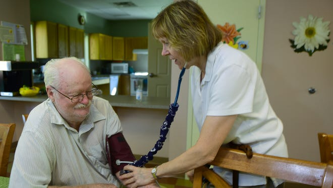 Community nurse Dee Parson takes John McGowan's blood pressure at Episcopal Square on Thursday morning, August 17, 2017 in Shippensburg.