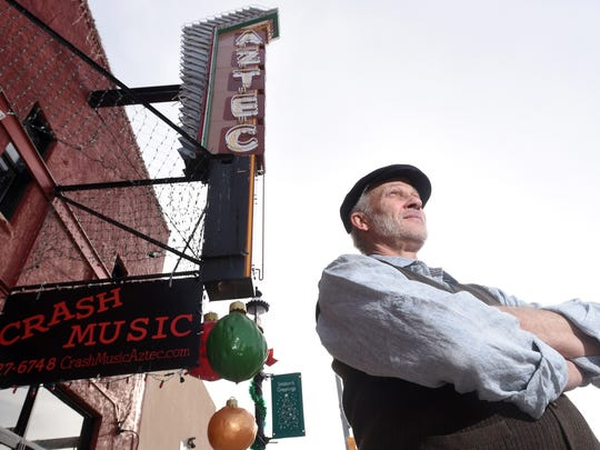 George Rowe, owner of Crash Music, stands in front of the historic Aztec Theater on Jan. 2.