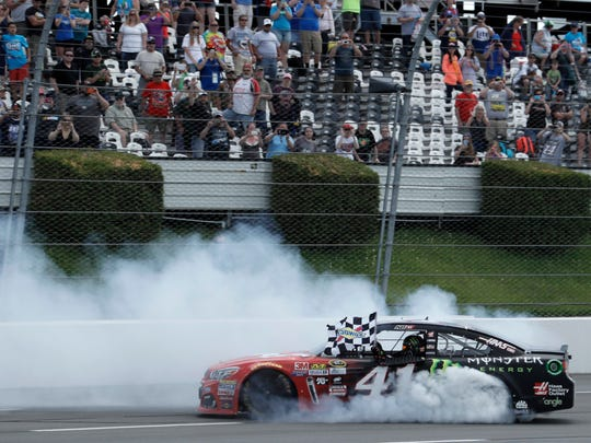Kurt Busch celebrates after winning the NASCAR Sprint Cup series auto race at Pocono Raceway, Monday in Long Pond.