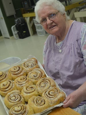 Grandma Ruth Grueneich, 85, holds up a tray of cinnamon rolls she just iced. She rubs icing on every roll. She learned to bake from her mother.
