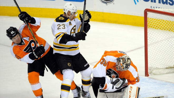 Philadelphia Flyers defenseman Kimmo Timonen (44) and Boston Bruins center Chris Kelly (23) battle as goalie Steve Mason (35) makes a save during the first period at Wells Fargo Center.