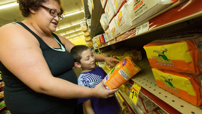 Nathaniel Guerrero, 8, and his mother Lyzette Jaco of Las Cruces check out the label on corn masa flour.