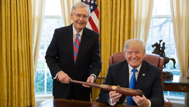 Sen. Mitch McConnell and President Donald Trump smile with a personalized Louisville Slugger bat to commemorate the passing of new tax legislation. Dec. 20, 2017