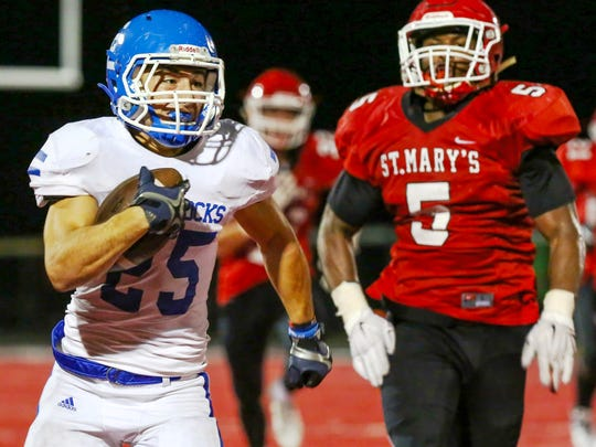 Catholic Central's Nicholas Capatina (left) races to