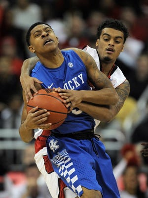 Kentucky's Tyler Ulis (front) ia wrapped up by UofL's Quentin Snider (back) on Saturday at the KFC YUM! Center. (By David Lee Hartlage, Special to the C-J) Dec. 27, 2014.