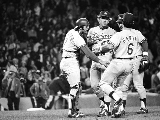 Dodgers Steve Yeager, left, Steve Garvey (6) and Ron Cey congratulate pitcher Burt Hooton, center, after he went all the way for the Dodgers  in a 6-1 win over the Yankees in second game of World Series in New York Wednesday, Oct. 12, 1977. (AP Photo)