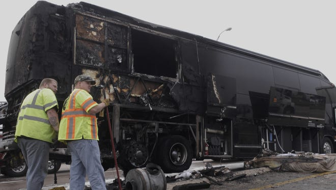 Workers clean up after a tour bus for superstar country group Lady Antebellum caught on fire a fire, Thursday, April 16, 2015 on eastbound I-30 in Garland, Texas. Singer Hillary Scott posted on the group's Facebook page that she, her husband, their tour manager and the driver were on the Dallas-bound bus when a tire caught fire.  Scott says everyone safely evacuated,  Garland police say the driver stopped the bus after the tire blew, and the vehicle caught fire on Interstate 30 just east of Dallas. Police confirm that nobody was injured. (Ron Baselice/The Dallas Morning News via AP) MANDATORY CREDIT; MAGS OUT; TV OUT; INTERNET USE BY AP MEMBERS ONLY; NO SALES