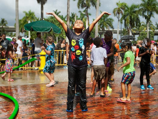 Royal Palm Elementary School third grader Cristopher Uscanga, 7,  cools off under the spray of a fire hose Sunday while waiting in line at the Big Backpack Event at the Harborside Event Center in downtown Fort Myers.
