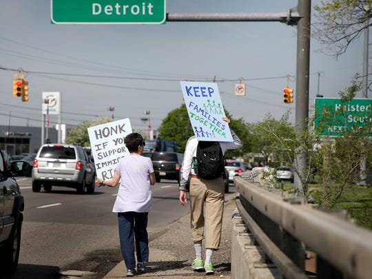 Cheryl Willette, left, and Glenn Maxwell walk through Farmington Hills on their third day of a 10-day march in support of immigrants from Detroit to Lansing on Wednesday, May 16, 2018.