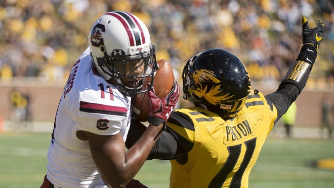 South Carolina wide receiver Pharoh Cooper, left, catches a pass over Missouri's Aarion Penton Saturday in Columbia, Mo.