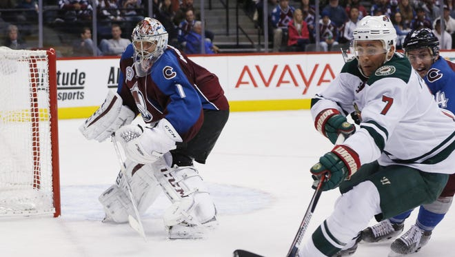 Minnesota Wild left wing Chris Porter, front right, reaches for the puck as it is cleared by Colorado Avalanche goalie Semyon Varlamov, left, of Russia, while Avalanche defenseman Tyson Barrie, back right, covers in the second period of an NHL hockey game Monday, Dec. 7, 2015, in Denver.