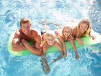 Family Outside Relaxing In Swimming Pool
