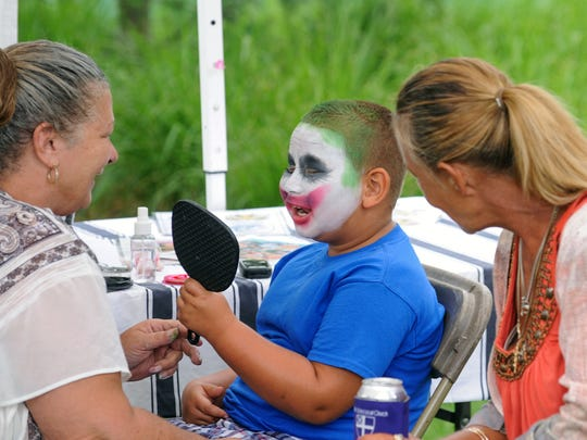 Six-year-old Korean Burbank is all smiles as his Joker face painting comes together during Saturday's 2016 Leilapalooza Music Festival.