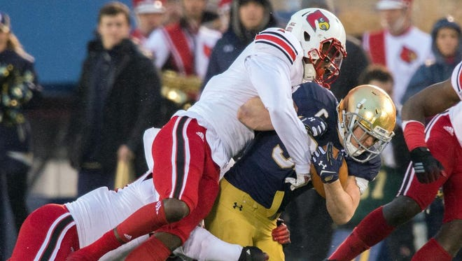 Nov 22, 2014; South Bend, IN, USA; Notre Dame Fighting Irish running back Cam McDaniel (33) is tackled by Louisville Cardinals safety James Sample (2) in the second quarter at Notre Dame Stadium. Mandatory Credit: Matt Cashore-USA TODAY Sports