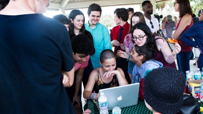 Emma Gonzalez, 18, center, a senior at Marjory Stoneman Douglas High School, is surrounded by her friends as she answers a social media message from actress and singer Zendaya at North Community Park on Sunday, Feb. 18, 2018. Gonzalez became a viral sensation after videos of her impassioned speech at an anti-gun rally in Fort Lauderdale flooded social media. Now, she is helping to lead the #NeverAgain movement with her fellow classmates.