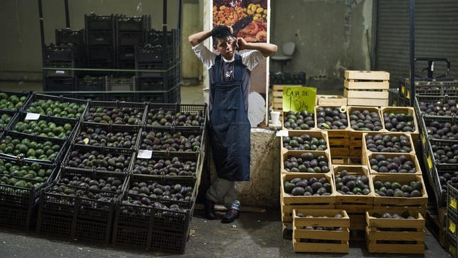 FILE - In this Aug. 9, 2016 file photo, an avocado vendor talks on his cellphone at a market in Mexico City. Summary: The potential Trump tariffs are expected to hit U.S. avocado lovers more than Mexican producers. (AP Photo/Nick Wagner, File)