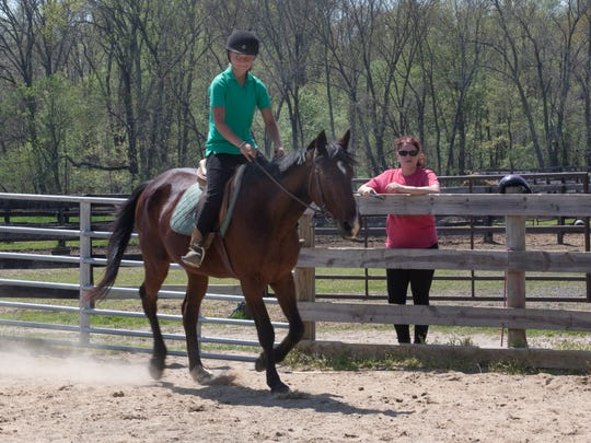 Wendy Morales watches as trainer Brielle Roman puts Clearly Possessed through his paces. Retired race horses that have been rescued and now live a farm in Monmouth County that are available for adoption. Morales is considering adopting.