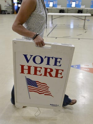 A poll worker in June carries out the Vote Here sign.