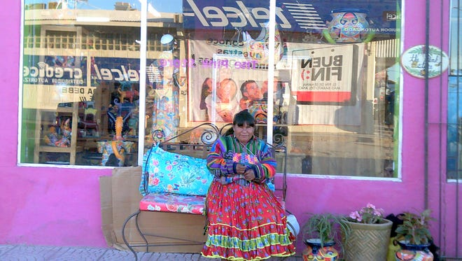 Marcelina, a Tarahumara native woman, holds the door for customers at the Pink Store in Palomas, Chih. Mexico. The Pink Store is arguably the hub of the town's business district.