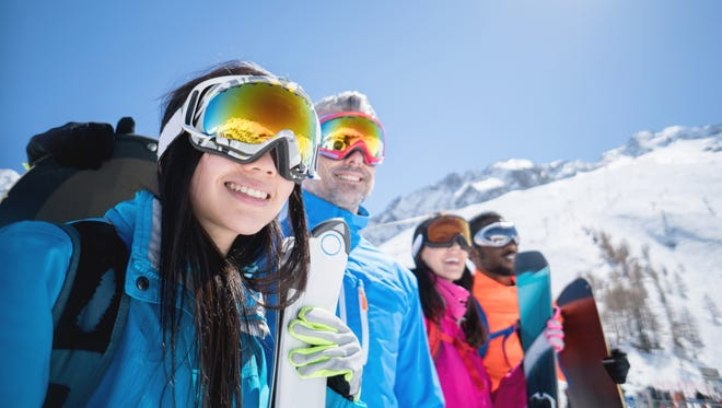 Happy group of people skiing and wearing goggles outdoors - winter sports concepts
