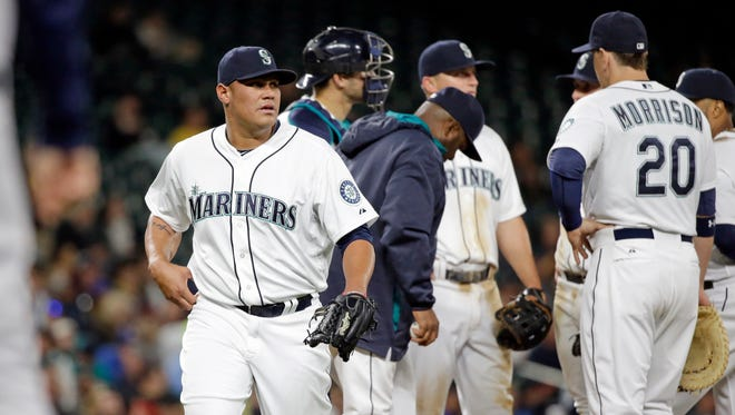 Seattle Mariners relief pitcher Yoervis Medina, left, leaves the game against the Houston Astros in a baseball game Monday, April 20, 2015, in Seattle.