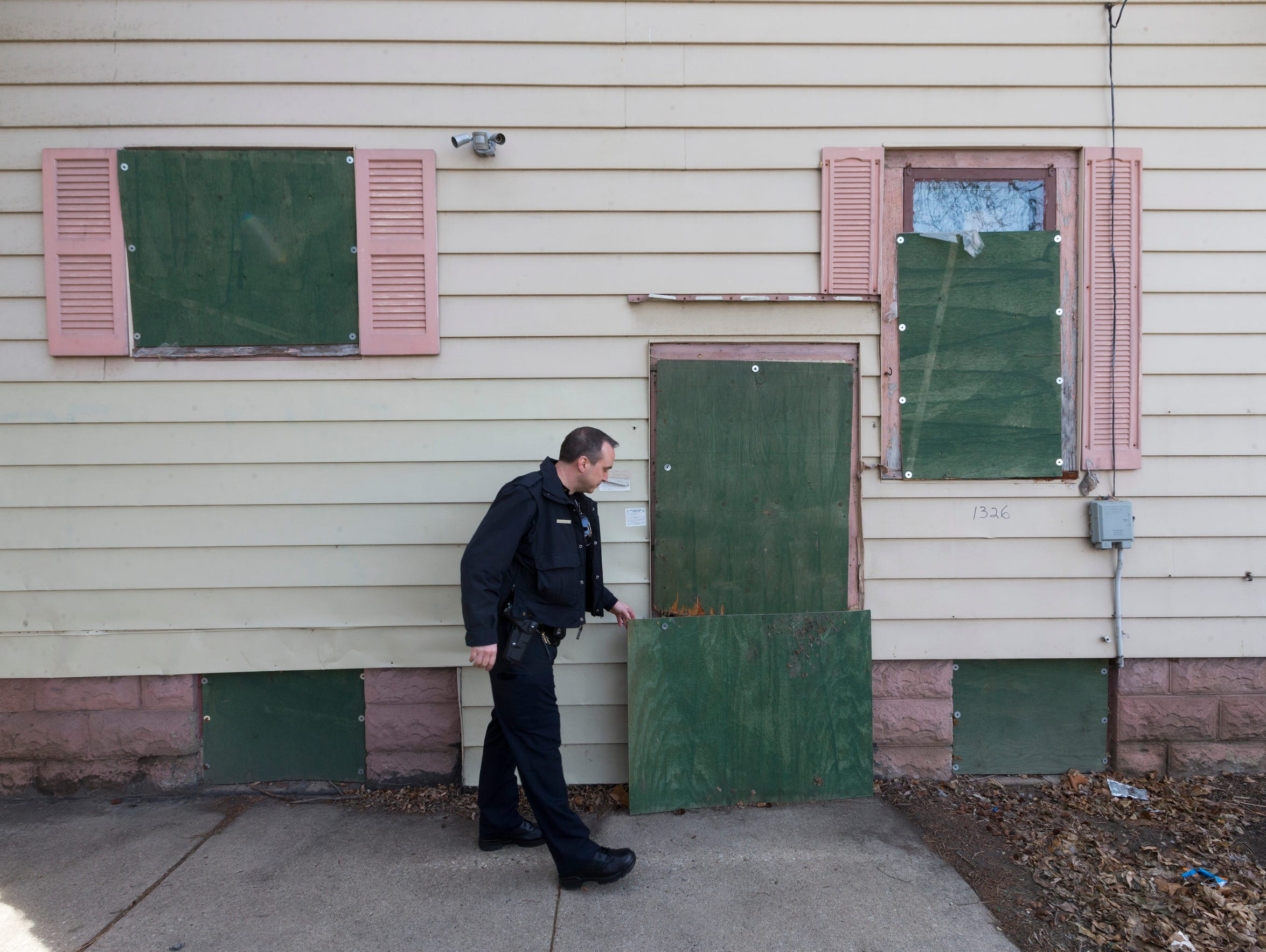 Milwaukee police officer Kevin Vodicka checks the condition of a boarded-up house Friday following a complaint from neighbors near S. 26th St. and W. Greenfield Ave. in Milwaukee.