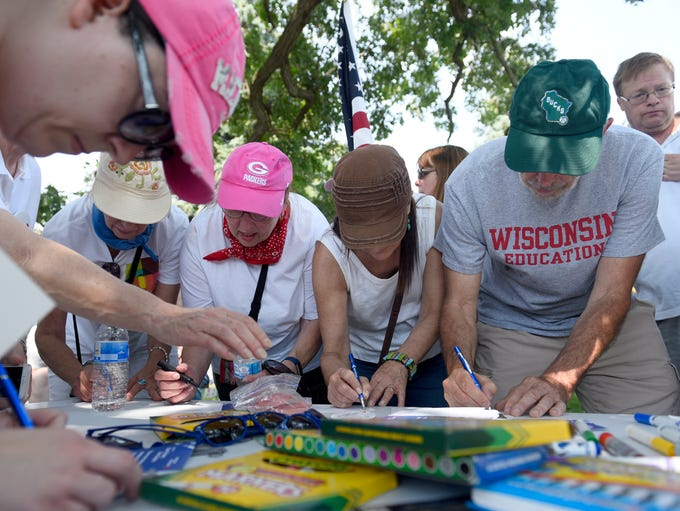 Protesters sign a pledge to vote in the November election