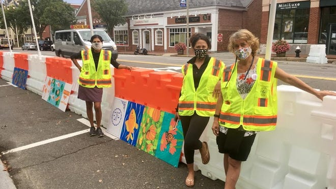 Upasna Chhabra, Innessa Manning, and Cristina Burwell install artwork on the barriers.