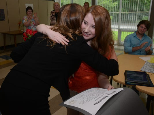 ANI Aiken Virtual Program graduate Jenifer Scott (left), principal of Aiken Virtual Program, hugs Kathryn Haston, 18, after presenting her with a high school diploma Wednesday, May 6, 2015. Haston completed all four years of high school through the online