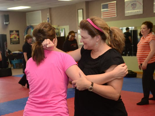 ANI Self Defense Class Virginia Norman (right) practices a defensive move on Brittany Dowden at a free self defense class at Master Rousseau's Taekwondo Saturday, May 9, 2015. Carol Rousseau, senior master, was teaching the free class in honor of Mother's