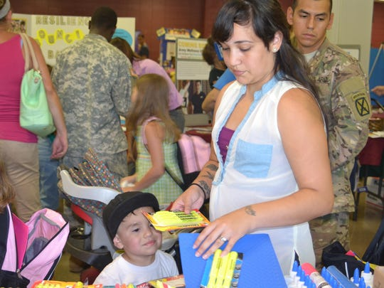 Ashley Zambrano picks up new highlighters and other school supplies for her children at Fort Polk's second annual Cafeteria Conversation, a large-scale informational fair at at North Polk Elementary School located on the post, on Tuesday. Also pictured are her husband, Sgt. Ricky Zambrano (back right), and their 2-year-old son A.J. (bottom left).