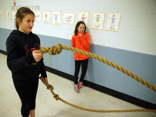 Lillianna Hansen, left, works out with the heavy ropes in the school gymnasium at Langlade Elementary School as Lillian Franzen watches.