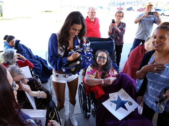 Dallas Cowboy cheerleader Jinelle greets residents at Trisun Care Center Coastal Palms in Portland on Wednesday, Dec. 20, 2017.