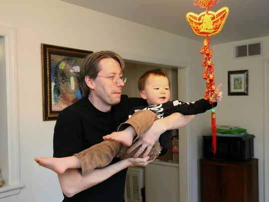 Clyde Hull and his son Corwin, 1, help the family decorate