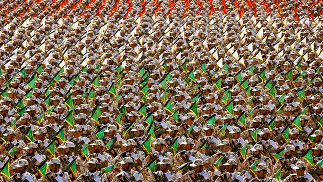 Members of the Iran's Revolutionary Guard march during an annual military parade marking the 34th anniversary of outset of the 1980-88 Iran-Iraq war, in front of the mausoleum of the late revolutionary founder Ayatollah Khomeini just outside Tehran, Iran, Monday, Sept. 22, 2014.
