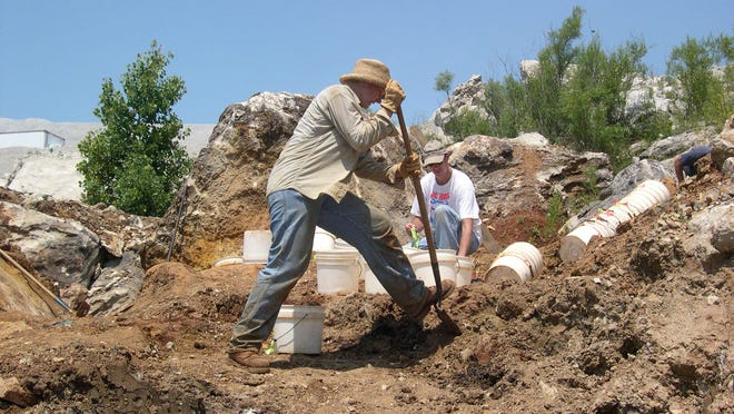 Michele Greenan, collections manager at the Indiana State Museum, shovels dirt into a bucket.