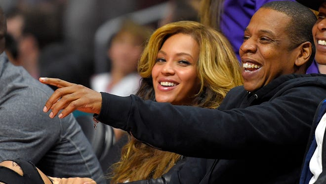 Singer Beyonce, left, and Jay-Z watch during the first half of an NBA basketball game between the Los Angeles Clippers and the Brooklyn Nets, Thursday, Jan. 22, 2015, in Los Angeles.