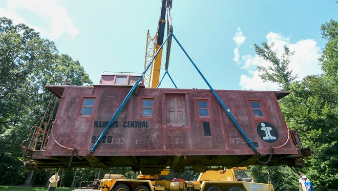 Construction and crane operators hoist up the body of a 1940s Illinois Central caboose to be places on the wheels on a track on the property of James and Deborah Grantham.