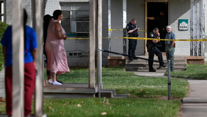 Neighbors watch Abilene Police Department officers investigate the scene of an officer-involved shooting at 4044 S. 7th St. Friday. Sgt. Lynn Beard said officers were serving a warrant to a resident of the apartment building when the man produced a gun.