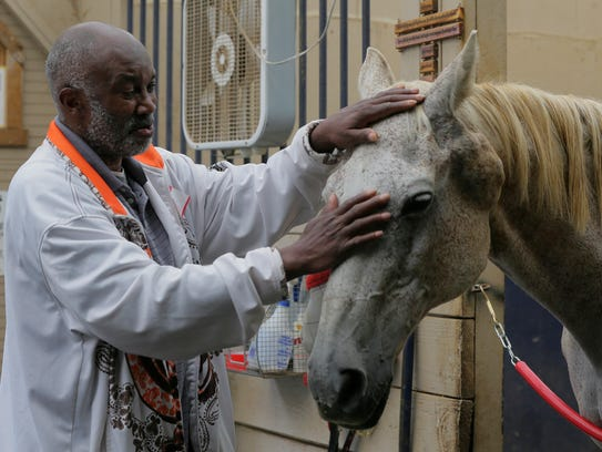 Dennis Cochran of Brooklyn, NY greets a horse named
