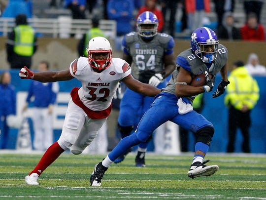 Nov 28, 2015; Lexington, KY, USA; Kentucky Wildcats wide receiver Dorian Baker (2) runs the ball against Louisville Cardinals linebacker Stacy Thomas (32) in the second half at Commonwealth Stadium. Louisville defeated Kentucky 38-24. Mandatory Credit: Mark Zerof-USA TODAY Sports