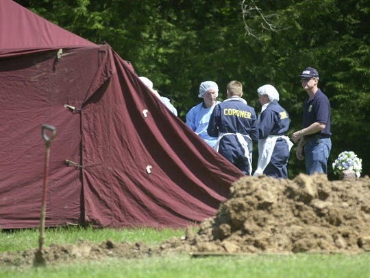 Officers from the Portage County Sheriff's Office and the Wisconsin Department of Justice exhume the body of Janet Raasch at St. Paul's Cemetery in Hamburg.