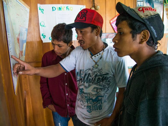 Carlos Gonzalez, 18 (left), Jose Hernandez, 28 (center), and Jairo Garniga, 16, study a map at a migrant shelter in Tecun Uman, Guatemala before preparing to cross the river into Mexico. The map warns of dangers along the route to the U.S., including natural dangers and criminal gangs that prey on migrants.