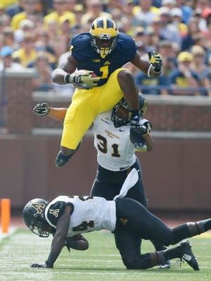 Michiganwide receiver Devin Funchess leaps Appalachian State's Dante Blackmon, bottom as Rashaad Townes tackles I'm from behind on a first down pass reception in the first quarter in their football game in Ann Arbor on Saturday, August 30, 2014.