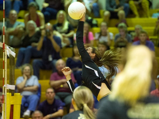 Sophomore Maddie Clabaugh leaps up to spike the ball